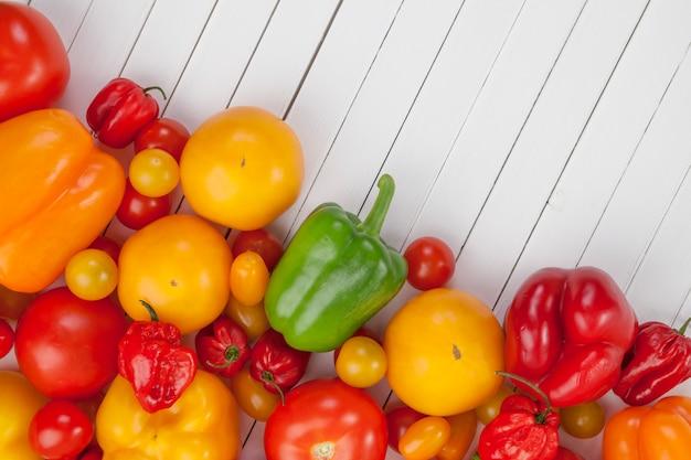 Kolorowi warzywa na biały drewnianym: pomidory i papryka, odgórny widok