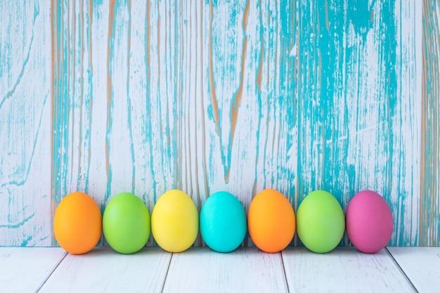 Kolorowi wielkanocni jajka na błękitnym drewnianym tle. kartka wielkanocna, tło, makieta paschalna, rama z pustej przestrzeni.