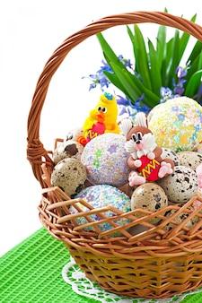 Kolorowi wielkanocni jajka w koszu na bielu