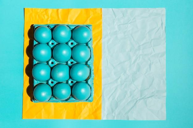 Kolorowi wielkanocni jajka w stojaku na papierze na stole