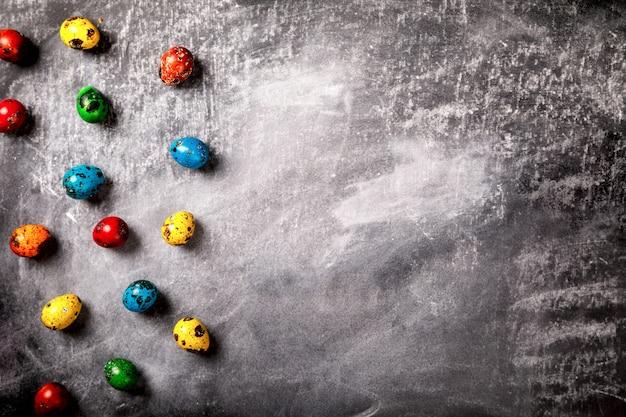 Kolorowi wielkanocni przepiórek jajka na czarnej tło kredzie