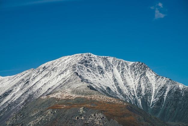Kolorowy alpejski krajobraz z wielką górą w jesiennych kolorach ze śniegiem na szczycie w promieniach słońca w błękitne niebo. malownicza jesienna sceneria z ośnieżonym szczytem górskim. niesamowity widok na żywy szczyt górski