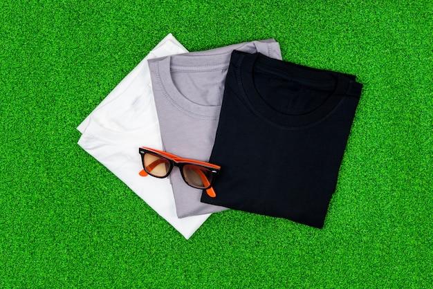 Kolorowy bawełniany t-shirt z okularami przeciwsłonecznymi na zielonej trawie.