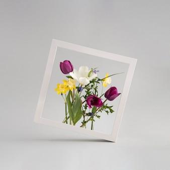 Kolorowy bukiet frower ułożony wewnątrz kwadratowej białej ramki na jasnoszarym tle. piękna kompozycja. poziomy układ zdjęć