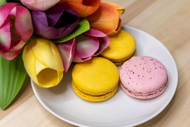 Kolorowy bukiet kwiatów z yellos i różowymi makaronikami na białym talerzu na stole woodent