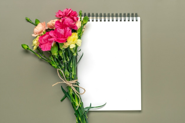 Kolorowy bukiet różnych różowych kwiatów goździków biały notatnik na zielonym tle