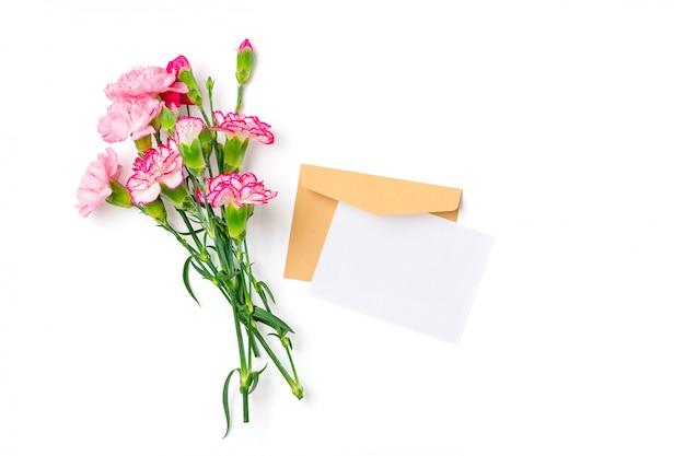 Kolorowy bukiet różnych różowych kwiatów goździków, koperta rzemiosła, papier na białym tle