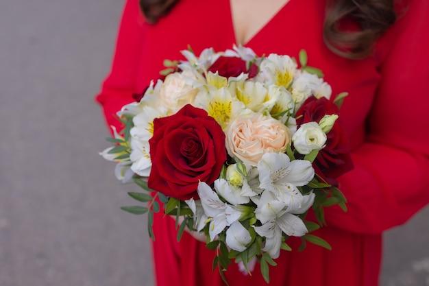 Kolorowy bukiet różnych świeżych kwiatów przed murem. bukiet storczyków, róż, frezji i liści eukaliptusa. rustykalne tło kwiat. widok z góry.