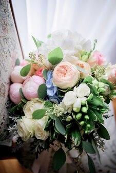 Kolorowy bukiet ślubny wykonany z peonii i róż stoi na krześle