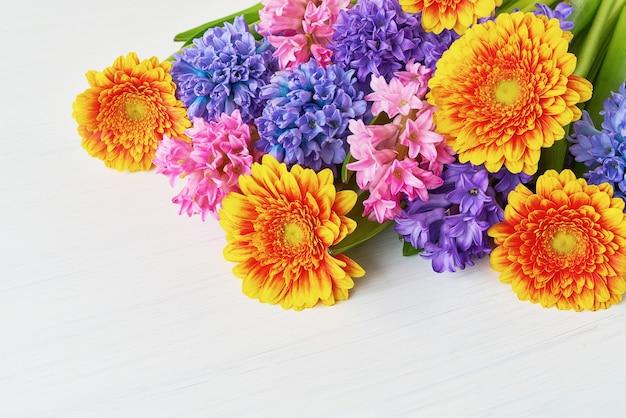 Kolorowy bukiet żółtych gerber i hiacyntów na białym tle. skopiuj miejsce. kartka z życzeniami.