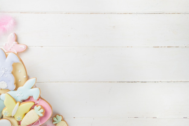 Kolorowy cukier wielkanocny symbol ciasteczka talerz na białym drewnianym stole. happy easter wiosna wakacje tło kopia przestrzeń