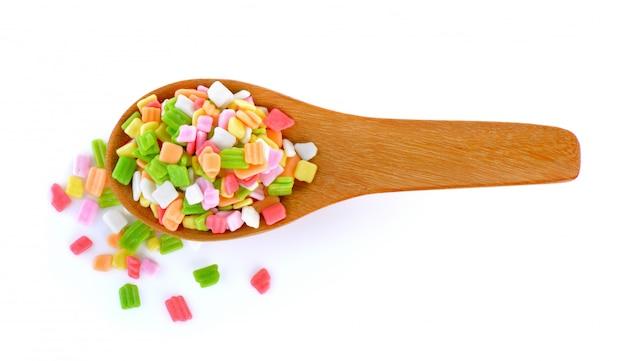 Kolorowy cukierek w drewnianej łyżce na biel ścianie