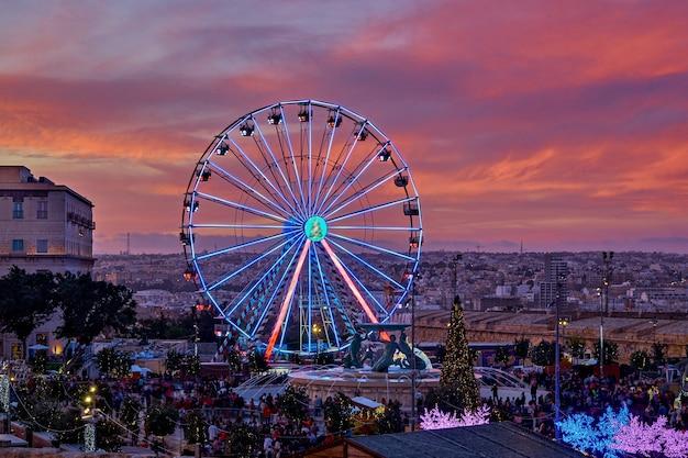 Kolorowy diabelski młyn przed zachód słońca różowe niebo i gród malta. jarmark bożonarodzeniowy w valletta malta widok z lotu ptaka, rozmycie ruchu, selektywne ustawianie ostrości