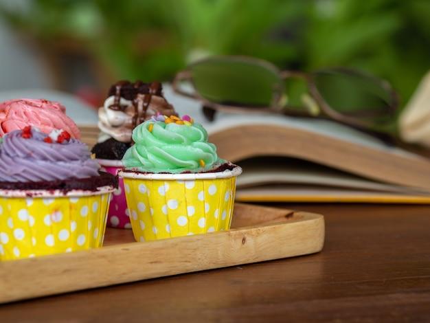 Kolorowy domowej roboty babeczka na drewnianej tacy dalej i otwiera książkę na drewnianym stole.