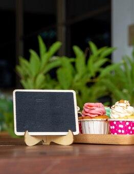 Kolorowy domowej roboty babeczka na drewnianej tacy z pustą blackboard i kopii przestrzenią dla twój