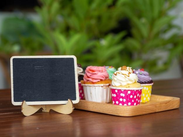 Kolorowy domowej roboty babeczka na drewnianej tacy z pustym blackboard