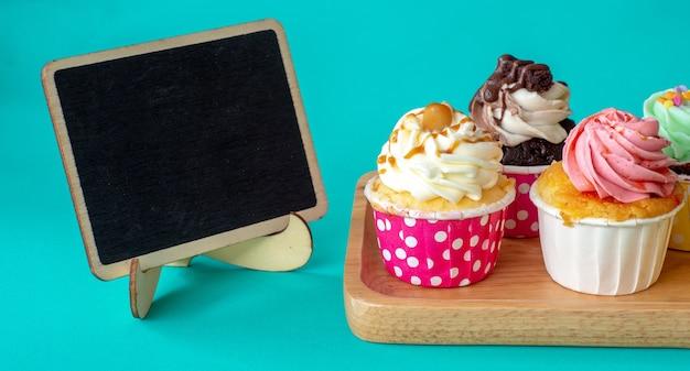 Kolorowy domowej roboty babeczka z pustą blackboard i kopii przestrzenią dla twój teksta.