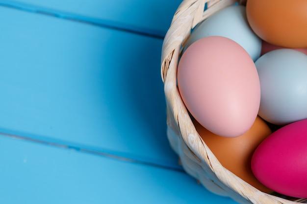 Kolorowy easter jajko w koszu na błękitnej drewno ścianie z przestrzenią.