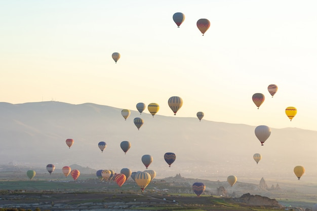 Kolorowy gorący powietrze balon lata nad czerwoną doliną przy cappadocia, anatolia, turcja.