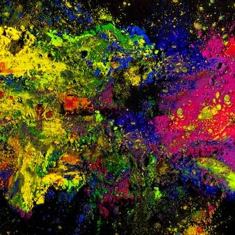 Kolorowy holi proszek bryzgający na czarnym tle