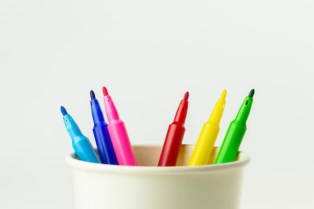 Kolorowy kolor pióro w białej papierowej filiżance kawy.