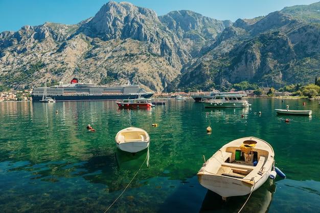 Kolorowy krajobraz z łodziami, statkiem wycieczkowym i jachtami w zatoce mariny, morze, góry, błękitne niebo. widok z góry na zatokę kotor, czarnogóra