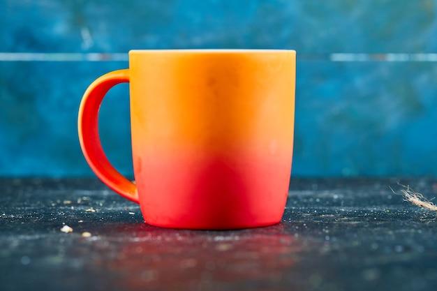Kolorowy kubek ceramiczny na niebieskim biurku.