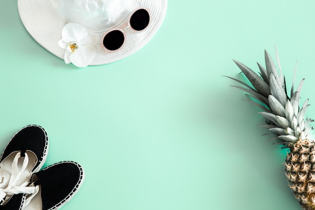 Kolorowy letni damski strój na płasko. biała stylowa damska czapka z okularami przeciwsłonecznymi i świeżym ananasem. letnia moda lub koncepcja podróży wakacyjnych