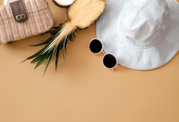 Kolorowy letni kobiecy strój leżący na płasko, biała czapka damska, okulary przeciwsłoneczne, torebka i świeży ananas.
