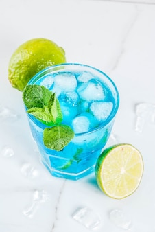 Kolorowy letni napój, mrożony niebieski alkoholowy koktajl laguny z limonką i miętą