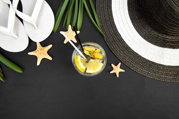 Kolorowy letni strój kobiecy. czarno-biały słomkowy kapelusz, klapki