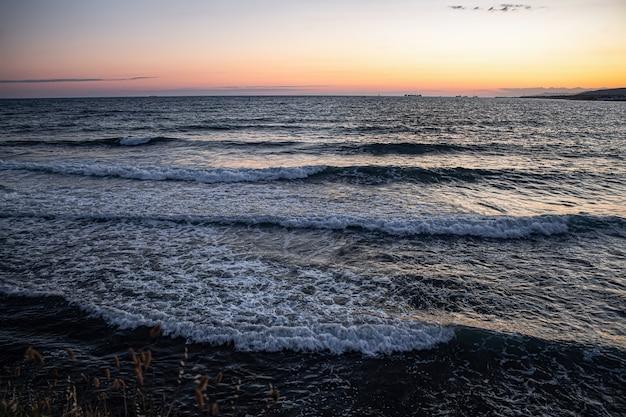Kolorowy letni zachód słońca nad morzem i fale morza czarnego w miejscowości wypoczynkowej gelendzhik.