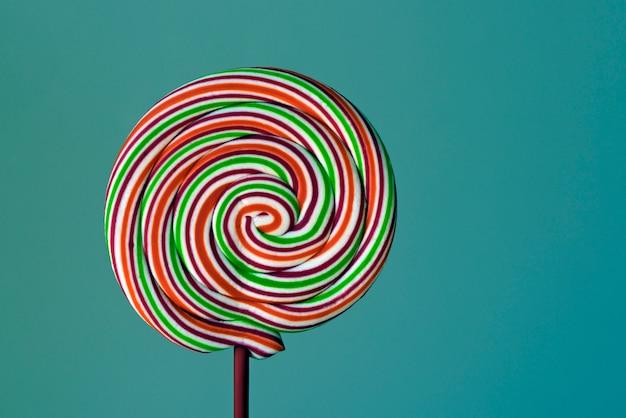 Kolorowy lizak w kształcie spirali na zielonym tle