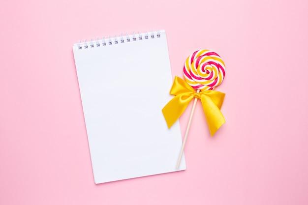 Kolorowy lizak z notatnikiem na różowo
