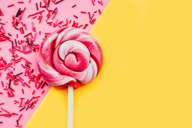 Kolorowy lizak z polewą cukrową na białym tle nad różową i żółtą ścianą papieru. leżał na płasko. skopiuj miejsce. minimalna koncepcja