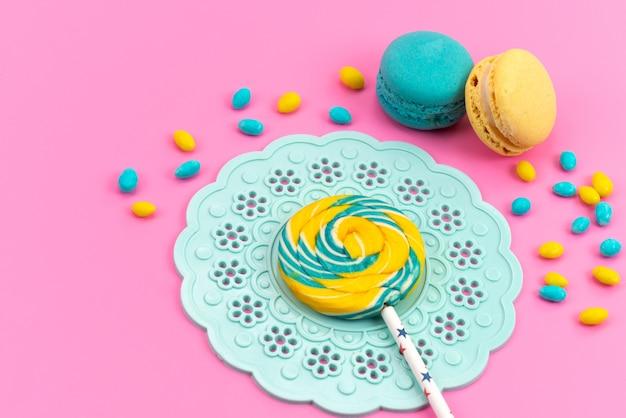 Kolorowy lizak z widokiem z góry z francuskimi makaronikami i cukierkami na różowym biurku, cukier słodki w kolorze cukierkowym