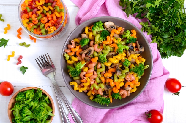 Kolorowy makaron cavatappi z brokułami i grzybami. makaron colorata makaron z warzywami widok z góry