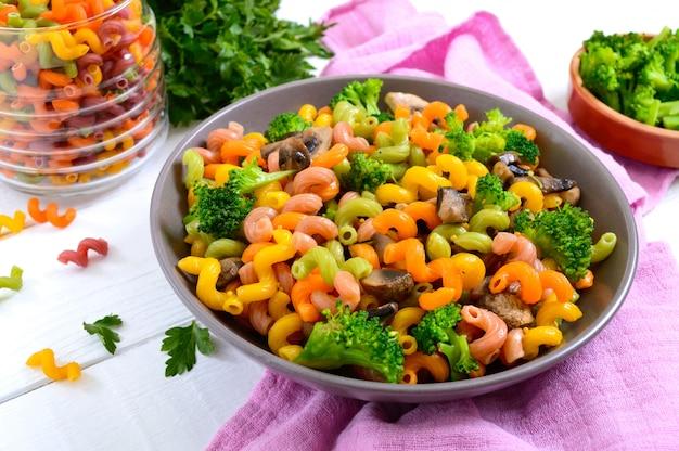 Kolorowy makaron cavatappi z brokułami i grzybami. makaron colorata makaron z warzywami