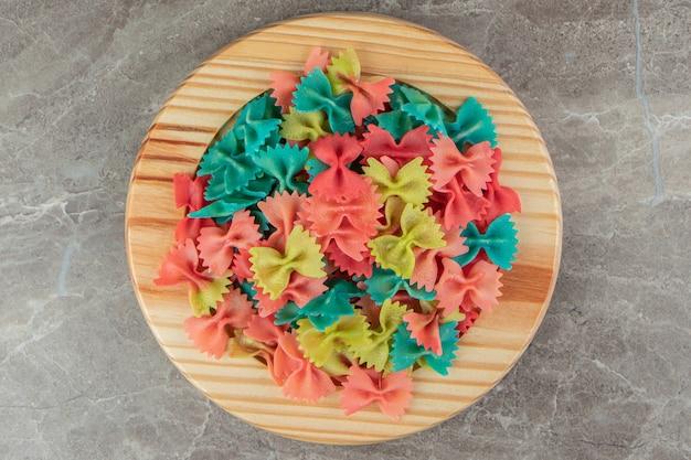 Kolorowy makaron farfalle na drewnianym talerzu