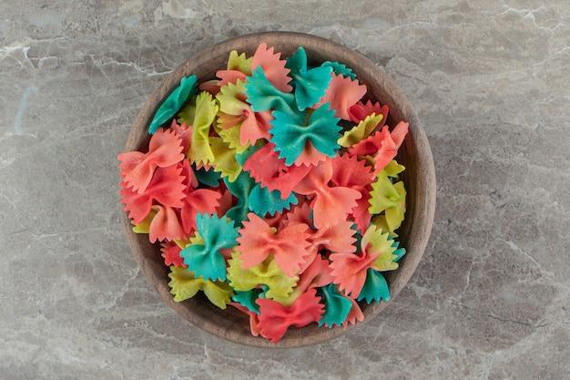 Kolorowy makaron farfalle w drewnianej misce