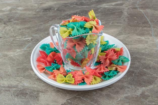Kolorowy makaron farfalle w szklanym kubku