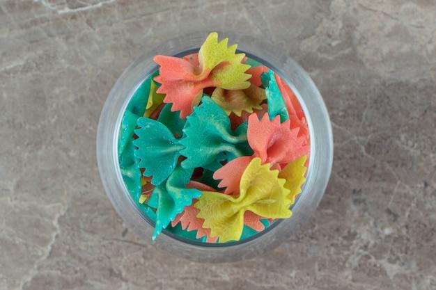 Kolorowy makaron farfalle w szkle na marmurowej powierzchni.