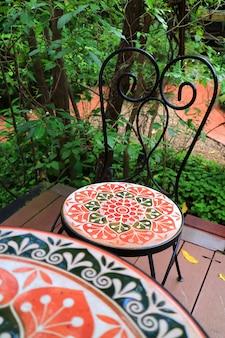 Kolorowy malujący kamienny krzesło przy taras zielenią w ogródzie z selekcyjną ostrością ,.