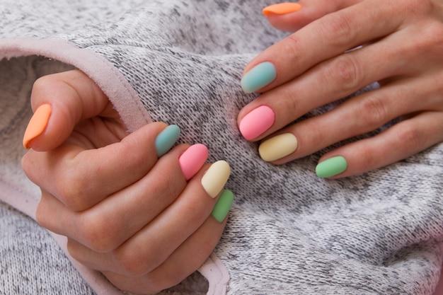 Kolorowy matowy manicure na kobiecych dłoniach na szarej powierzchni