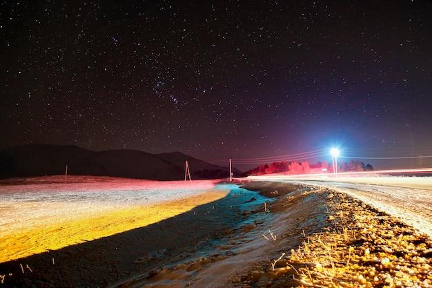 Kolorowy nocny krajobraz z długim czasem ekspozycji z górami i drogą w zimie