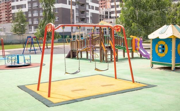 Kolorowy nowoczesny plac zabaw na dziedzińcu w parku bez ludzi. huśtawka, karuzela zewnętrzna dla dzieci. plac zabaw w publicznym parku otoczony zielenią i nowymi domami. dzieci ćwiczą.