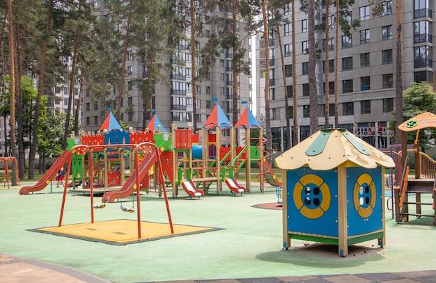 Kolorowy nowoczesny plac zabaw na podwórku w parku bez ludzi. plac zabaw dla dzieci w publicznym parku otoczonym zielenią i nowymi domami. ukraina, kijów - 29 czerwca 2021 r.