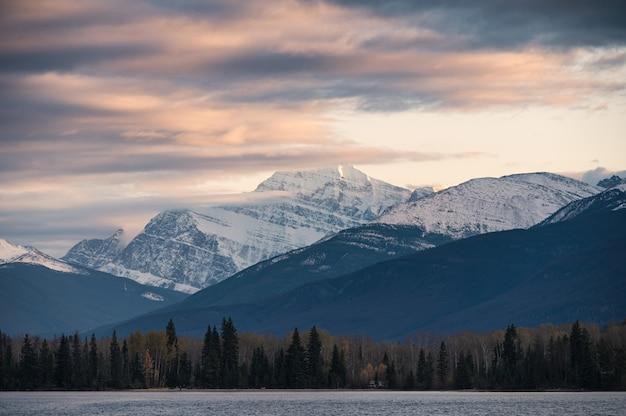 Kolorowy obłoczny przepływ przez skalistej góry na wieczór