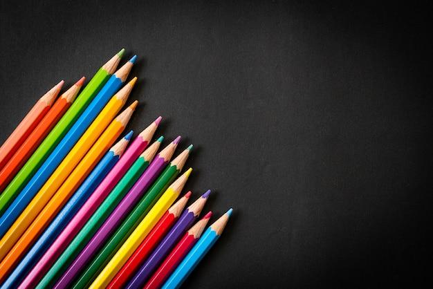 Kolorowy ołówek na czarnym tle z miejsca na kopię
