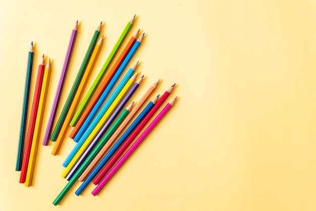 Kolorowy ołówek na żółtym tle z miejsca na kopię